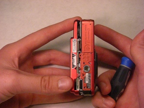 Gently remove the back casing by holding onto both sides of the camera and pulling them apart.