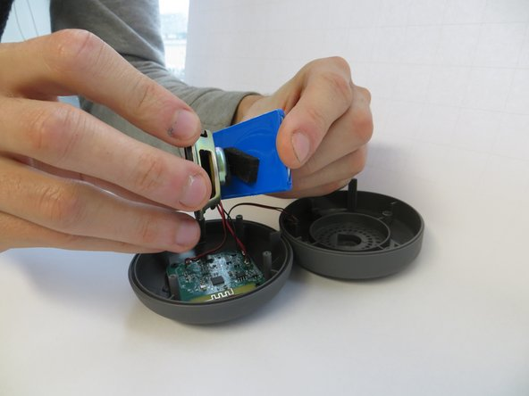 Separate the battery from the speaker by pulling gently. The foam adhesive will release.