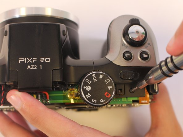 Remove one 4-mm screw using a J000 screwdriver from the top of the camera, near the mode dial.