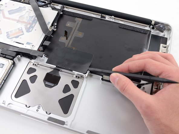 Image 1/2: Peel the tape up and fold it back out of the way of the trackpad cable. Leaving it in place on the upper case will make it easier to reapply it during reassembly.