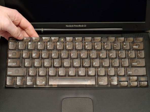 Lift the keyboard out by pulling it up and away from you. Rest the keyboard, face down, on top of the trackpad.