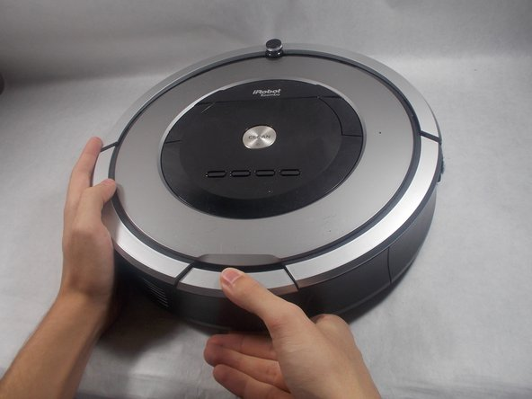 Orient the Roomba so that the device is on its wheels and the words can be read from left to right.