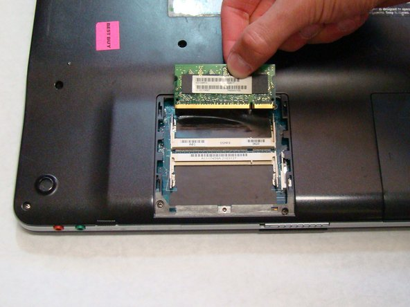 Image 3/3: Use your fingers to grab the raised edge of the RAM and pull the chip away from its connection to the laptop.