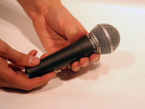 Grab the microphone base with one hand. With the other hand, grab just below the grille (the collar). Twist the collar clockwise to loosen it.