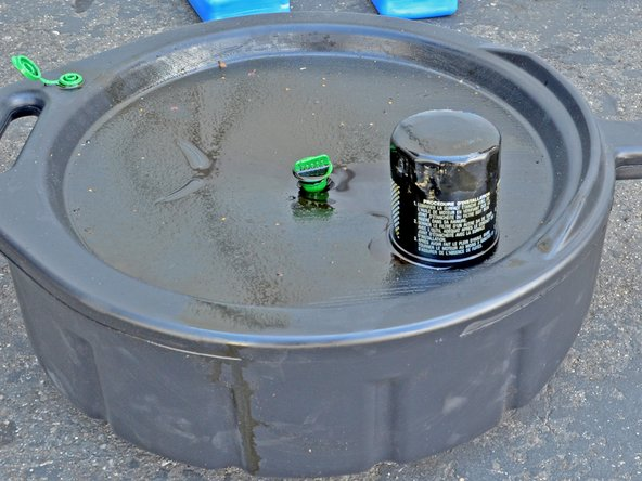 Image 1/2: Place your old oil filter face down in your oil drain pan and allow 12-24 hours for all the oil to drain out.