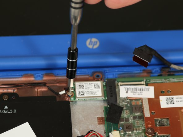 Remove the 3.5 millimeter screw from the WiFi chip using a #00 Phillips head screwdriver.