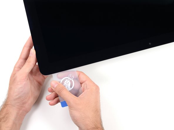 Slide the card toward the center of the display to cut any of the remaining adhesive along the top right corner of the iMac.