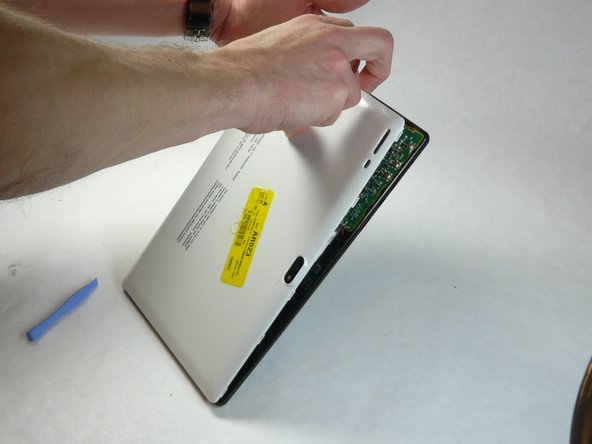 Remove back case of tablet by taking spudger tool to lift the back plate.
