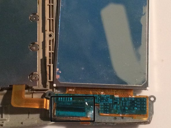 Flip over the LCD and button assembly to the right, and if covered, peel the tape on the back of the button assembly back to expose a ribbon connection.