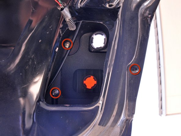 Image 1/3: The black nut at the edge of the trunk lid has an extended round end that prevents a standard 8 mm socket from seating fully. You can use a regular socket if you can keep the bit level while rotating, but a deep socket is recommended to prevent stripping.