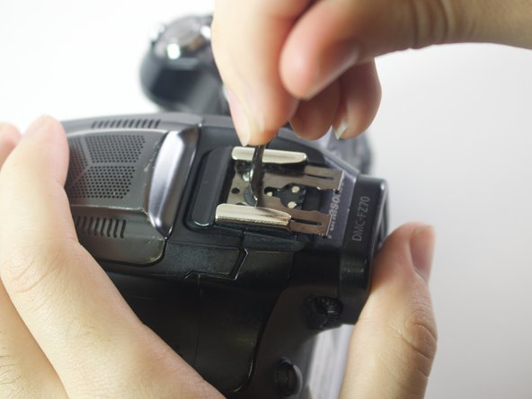 With a metal spudger, lift this sheet and push it out of the rail device to detach it from the camera.