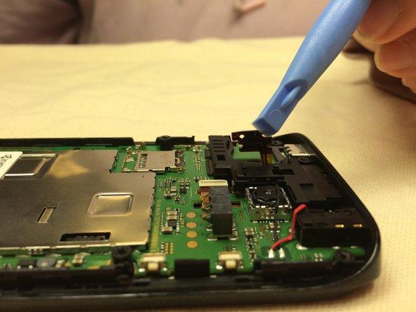 La puce est connectée au téléphone par un petit fil orange. Gardez le fil connecté à la puce et le corps du téléphone tout en retirant la puce de l'enveloppe en plastique noir.