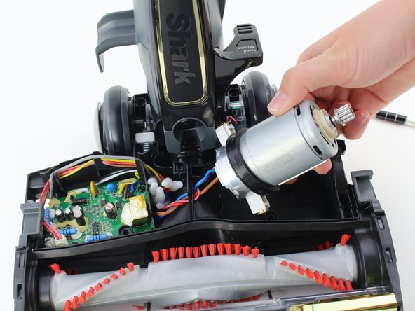 With both thumbs, push the gear on the right side of the motor into the vacuum. The motor should pop out.