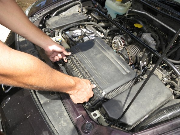 Begin by opening the hood of the vehicle and locating the air filter cover.