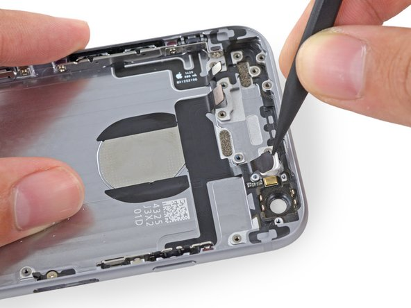 Image 2/3: If you encounter significant adhesive, use tweezers to peel the components up from the rear case.