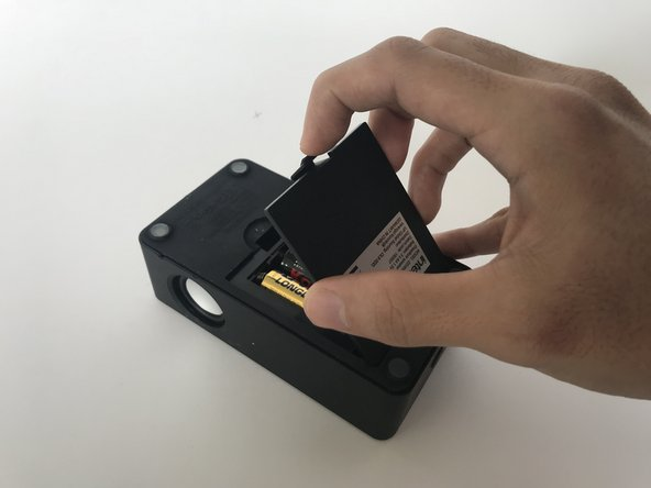 Squeeze latch, tilt and remove battery cover to retrieve the batteries.
