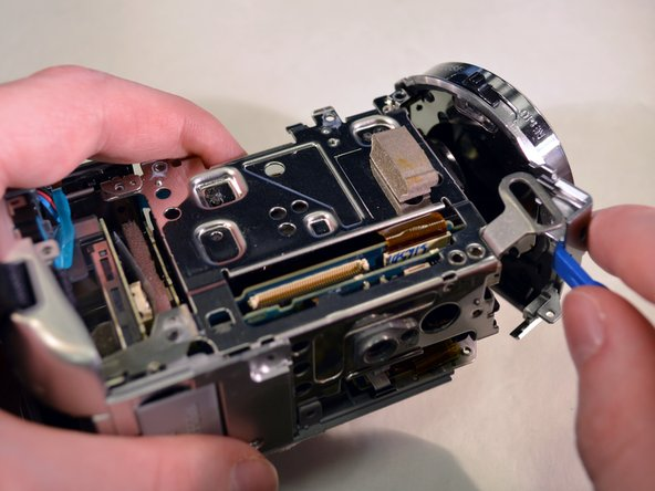 While securing the device with your left hand, use gentle rightward pressure with a plastic opening tool to pop off the shutter assembly. To do this, position the plastic opening tool in the slot labeled in photo one. A close up of the shutter assembly in the picture might help also.