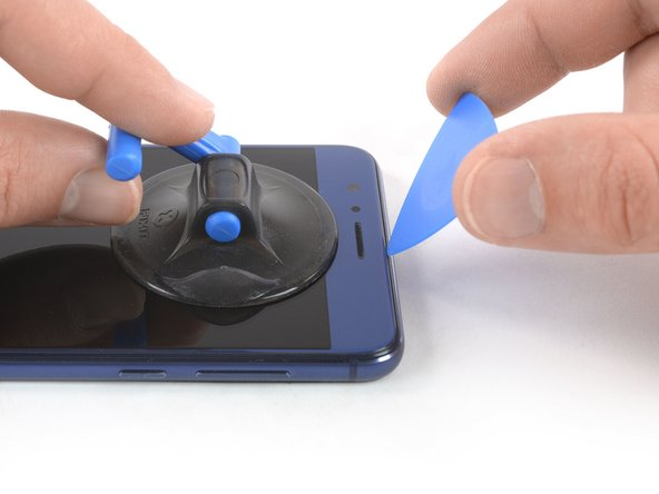 Once the screen is warm to the touch, apply a suction cup near the top edge of the phone right under the earpiece speaker.