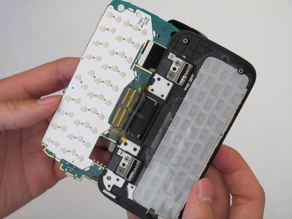 Flip the motherboard over, as if you are turning a page in a book, so that it rests on the back side of the screen.