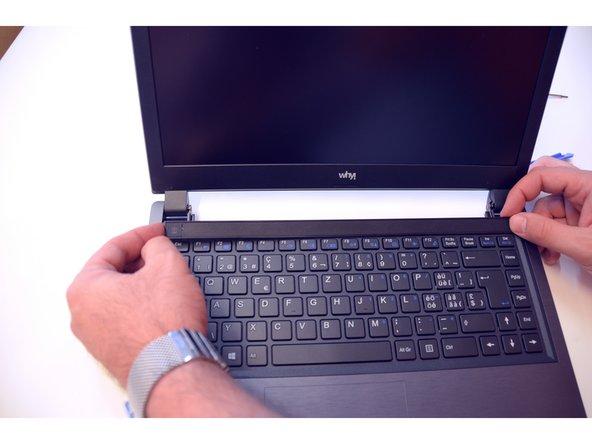 Drehen Sie dann den Laptop um und befreien Sie die Abdeckungs-Leiste.