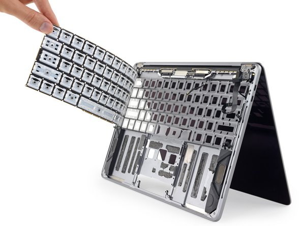 With all of its defenses thwarted, the keyboard PCB gives way and peels from the chassis, fully exposing the membrane that was sandwiched underneath.