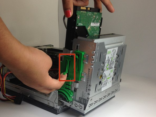 Use your right index finger to pull forward the green flap on the side of the hard drive.