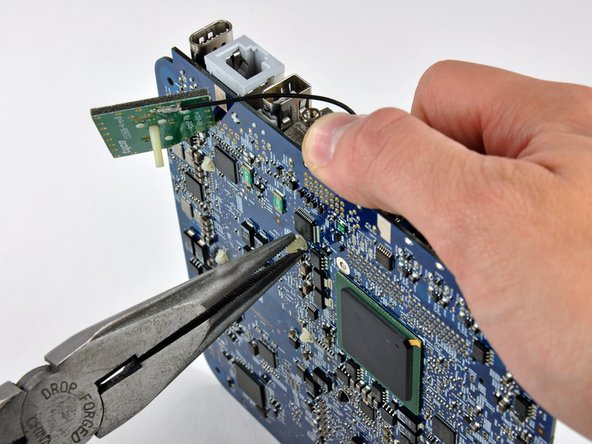Image 2/2: While holding the pin down from the heat sink side of the board, use a pair of pliers in your other hand on the underside of the board to squeeze both barbs against the plastic shaft of the pin.