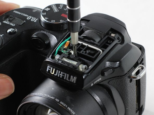 Use a PH00 screwdriver to unscrew the 0.5m screw located at the center of the flash pop up