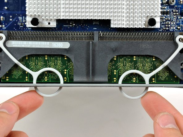 Push the two RAM arms protruding from the access door inward and set them on the lower edge of the rear case to prevent them from getting caught when removing the logic board.