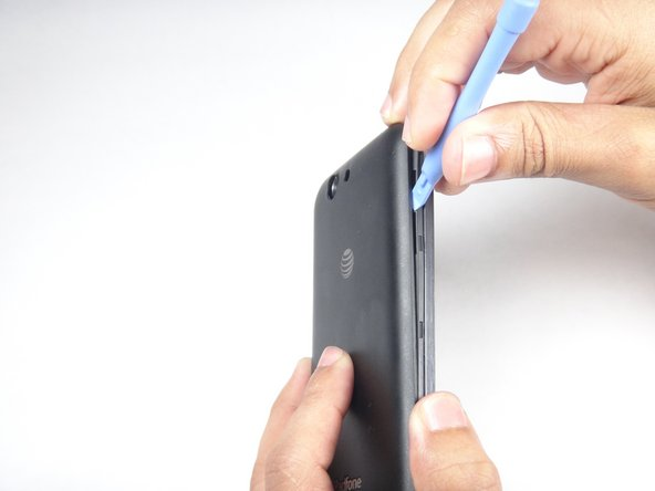 Using the blue plastic opening tool, insert the tip into the crease between the back cover and the phone and pry it upwards.