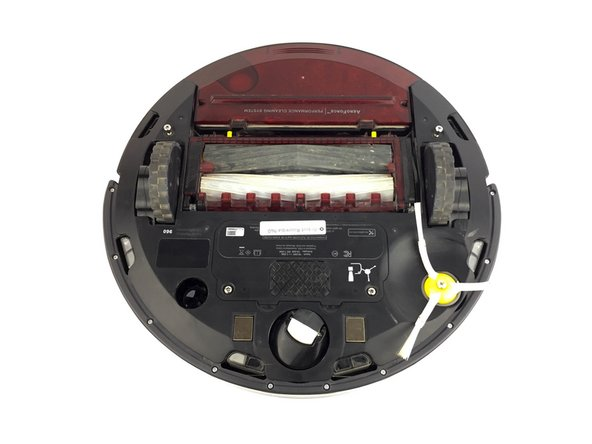 Turn the Roomba upside down and orient it so that the wheels are facing upwards and the dustbin is furthest from you.