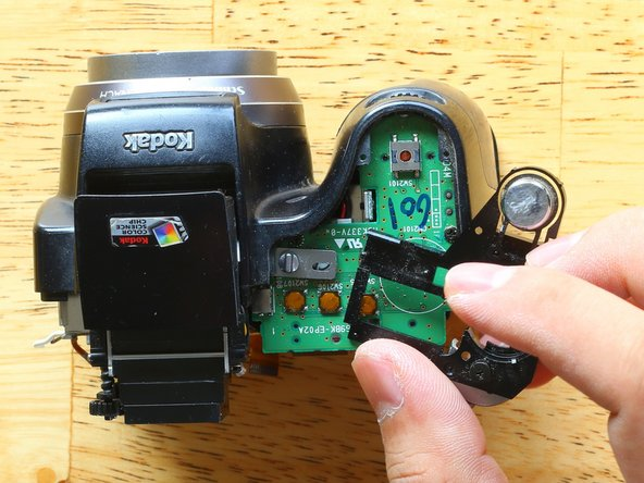 Once the mechanical flash switch is loose, you can remove the top black plastic part.