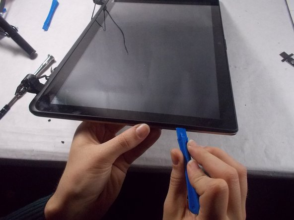 Use the plastic opening tool to pry the plastic covering off of the monitor.