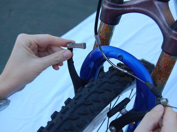 Unhook the brake wire in the metal tube from the brake wire holder on the brake caliper in your left hand.