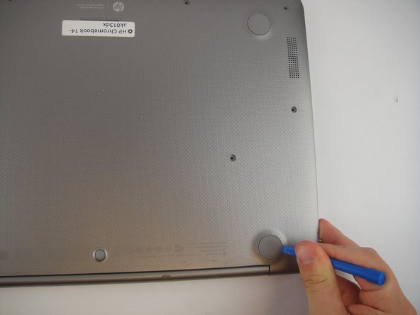 Using a plastic opening tool or another prying device, remove the five rubber stoppers on the upper side of the laptop to reveal screws.