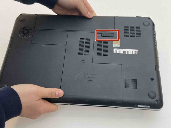 Pull the slide release tab to the left to free the battery.
