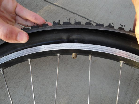 Remove the tube by pushing the valve through the hole in the rim and pulling the tube out from under the tire.