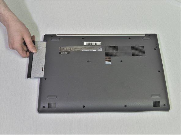 Entferne sorgfältig die Halterung des optischen Laufwerks, indem du die Einfassung vom Laptop wegziehst.