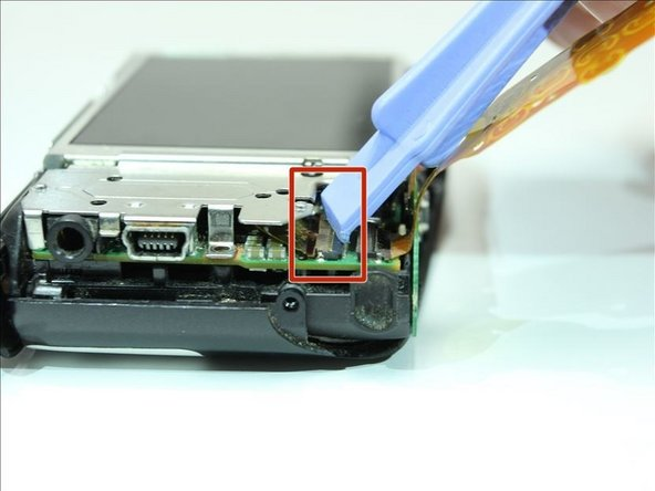 Image 1/2: Lift up the flap with a plastic opening tool.