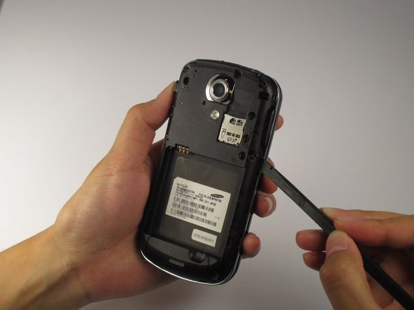 Using a prying tool, separate the back housing from the silver trim around the phone.