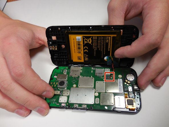 Gently lift the back plate away, exposing the motherboard. The battery will be stuck to the back of the cover, so be careful when lifting it off.