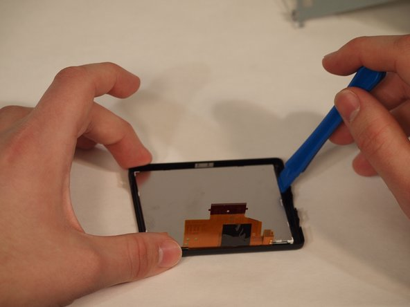 The screen is glued into the casing. Remove the screen by carefulyl lifting along the edges of the case until the screen pops out. Place new screen into the existing casing. A small about of glue or adhesive may be necessary if their isn't sufficient adhesive remaining in the case. Repeat steps in reverse to reapply screen.