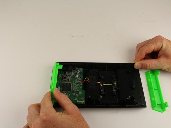 Use your hand to gently pull the green side plates away from the center of the device.