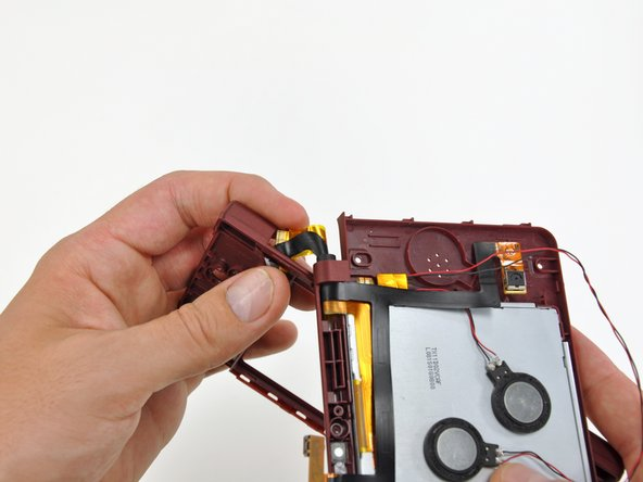 Rotate the front bezel assembly clockwise so that the ends of the camera and LCD cables slide sideways through the slit in the front bezel.