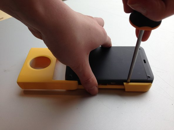 Turn the Waka Waka upside down. Make sure the Waka Waka is placed on a flat surface. Place the flathead screwdriver between the yellow and the black part as can be seen in the second picture. Force will be needed. If one side came loose, do the same for the other side.