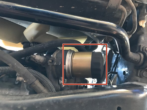 Image 1/1: Slide the oil drain pan below the oil filter so that it will catch any oil that drips down when the oil filter is removed.