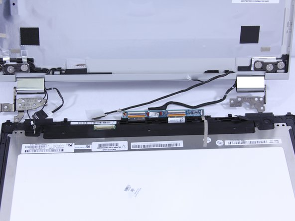 Lift the circuit board out of the way to expose the wire underneath. Remove the wire from the base of the laptop.