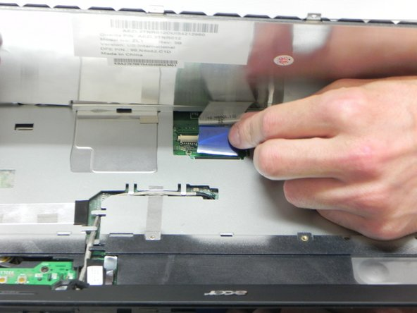 Lift the ZIF connector's black retaining flap. Then  gently slide the ribbon cable out.