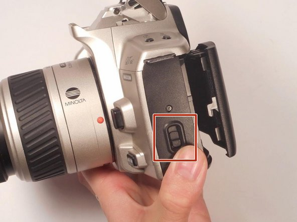 Press the release button on the side panel to pop open the back piece of the camera.