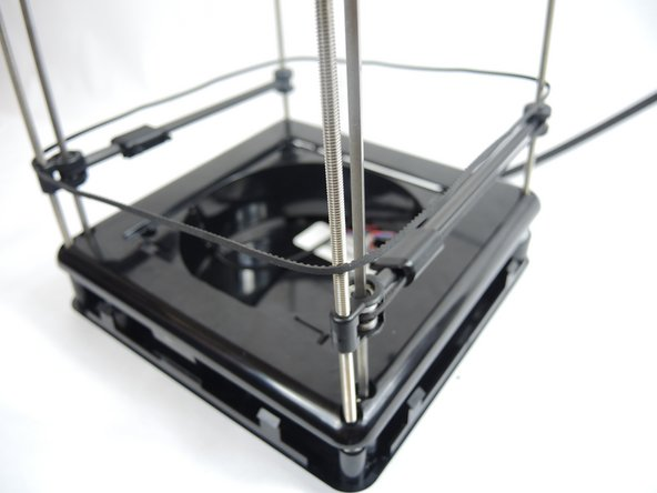 Remove the z axis belt from the device by simply lifting each corner of the belt off the corner gears and slide up over the z axis bars.